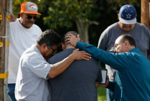 A group of men embrace in prayer on on Dec. 3, 2015, outside the crime scene where the suspects in the shooting at the Inland Resource Center were killed in San Bernardino. (Credit: Sean M. Haffey/Getty Images)