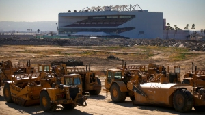 "Giant machines called ""scrapers"" are moving the dirt and changing the landscape of the former Hollywood Park site in Inglewood where an NFL stadium will eventually be constructed. (Credit: Mark Boster/Los Angeles Times)"