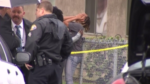 A woman is distraught at the scene of a fatal shooting in Long Beach on Dec. 22, 2015. (Credit: KTLA)
