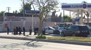 Officials investigate a deadly shooting in Lynwood on Dec. 12, 2015. Two sheriff's deputies opened fire on a man they say was armed with a gun. (Credit: KTLA)