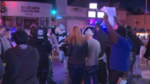 Dozens of people gathered, several apparently angry, after video emerged showing deputies fatally shooting a man in Lynwood on Dec. 12, 2015. (Credit: KTLA)
