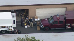 Investigators work on Dec. 3, 2015, in the garage area of a Redlands home rented by the couple who opened fire in San Bernardino the previous day. (Credit: KTLA)
