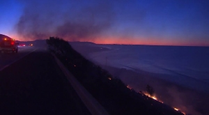 The Solimar Fire is pictured as the sun rises over the 101 Freeway in Ventura County on Dec. 26, 2015. (Credit: KTLA)