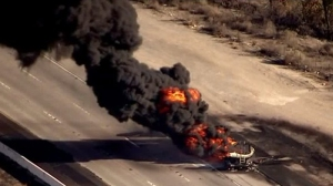 A burning tanker truck sends up a plume of thick black smoke on the 15 Freeway near Lake Elsinore on Dec. 1, 2015. (Credit: KTLA)