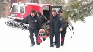 Rescuers carry a woman to an ambulance after she was found, barefoot and injured, near Wrightwood on Jan. 10, 2016. (Credit: KTLA)