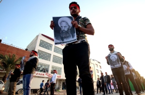 Shiite Muslim Iraqis, including supporters of the Shiite group Asaib Ahl al-Haq (The League of the Righteous), hold portraits of prominent Shiite cleric Nimr al-Nimr during a demonstration in the Iraqi mainly Shiite southern city of Basra on Jan. 6, 2016, against al-Nimr's execution by Saudi authorities in Saudi Arabia the previous week. (Credit: HAIDAR MOHAMMED ALI/AFP/Getty Images)