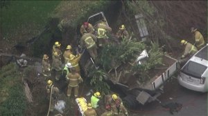 Firefighters work to extricate a driver from a truck that crashed in the 800 block of Loma Vista Drive in Beverly Hills on Jan. 15, 2016. (Credit: KTLA)