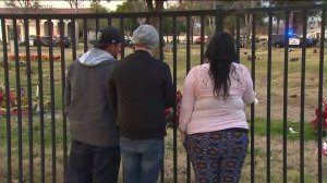 Onlookers peer through a fence after a fatal triple shooting occurred at a cemetery in Bellevue Memorial Park cemetery in Ontario on Jan. 2, 2015. (Credit: KTLA)
