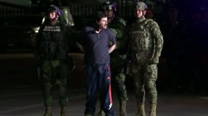 "Mexican forces escorted Joaquin ""El Chapo"" Guzman out of an armored vehicle and into a helicopter late Friday night following his arrest after months on the run. (Credit: CEPROPIE via CNN)"