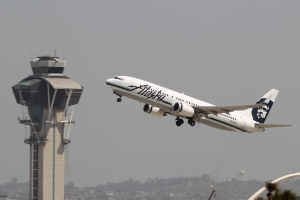 An Alaska Airlines jet passes the air traffic control tower at Los Angles International Airport during take-off on April 22, 2013. (Credit: David McNew/Getty Images)