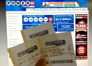 This January 10, 2016 photo illustration taken in Washington, DC, shows Powerball lottery tickets in front of the splash screen for the powerball.com website. (Credit: KAREN BLEIER/AFP/Getty Images)