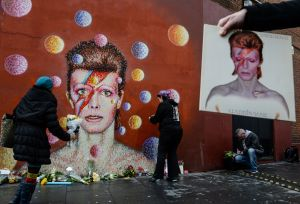 "A man holds a copy of the David Bowie album ""Aladdin Sane"" as floral tributes are left beneath a mural of the British singer painted by Australian street artist James Cochran, aka Jimmy C, following the announcement of Bowie's death, in Brixton, south London, on Jan. 11, 2016. (Credit: AFP PHOTO / CHRIS RATCLIFFE) RESTRICTED TO EDITORIAL USE, MANDATORY MENTION OF THE ARTIST UPON PUBLICATION, TO ILLUSTRATE THE EVENT AS SPECIFIED IN THE CAPTION / AFP / CHRIS RATCLIFFE (Photo credit should read CHRIS RATCLIFFE/AFP/Getty Images)"