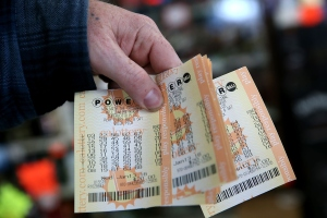 A customer holds a handful of Powerball tickets at Kavanagh Liquors on Jan. 13, 2016, in San Lorenzo. (Credit: Justin Sullivan/Getty Images)