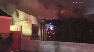 Firefighters battle a blaze that burned through a home in Norwalk on Jan. 22, 2016. (Credit: KTLA)