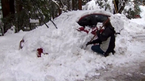 A Forest Falls resident digs a vehicle out of the snow post-storm on Jan. 8, 2016. (Credit: KTLA)