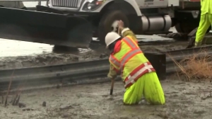 A Caltrans worker tries to clear mud from below the Solimar Fire burn area on Jan. 5, 2016. (Credit: KTLA)