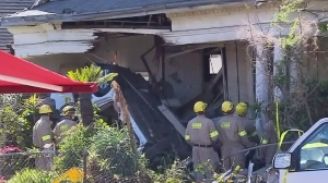 Two people were killed, including a female occupant whose body was trapped, when a vehicle crashed into a Boyle Heights home on Feb. 7, 2016. (Credit: KTLA)