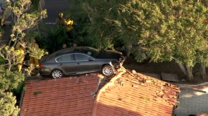 A vehicle landed on top of the roof of a Palos Verdes Estates home on Feb. 3, 2016. (Credit: KTLA)