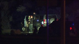 A man involved in a pursuit in Orange County could be seen holding a small child next to an SUV as another child looks out of the sunroof on Feb. 29, 2016. (Credit: KTLA)