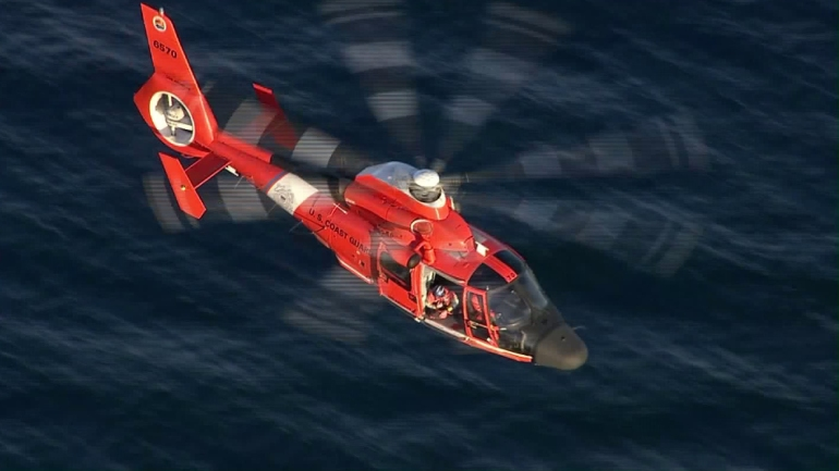 A U.S. Coast Guard helicopter searches the area after an apparent midair collision left two planes in the water of L.A. harbor on Feb. 5, 2016. (Credit: KTLA)