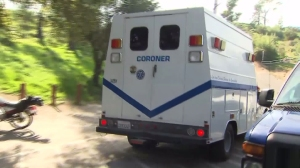 A coroner's van is seen at the scene below where human remains were found above Altadena on Feb. 22, 2016. (Credit: KTLA)