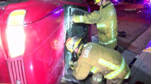 Fire crews work to rescue a trapped driver after a vehicle overturned in Garden Grove on Feb. 21, 2016. (Credit: OnScene.TV)