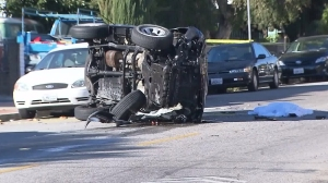 A body covered with a sheet is seen next to a vehicle that rolled over after a crash on Feb. 6, 2016. (Credit: KTLA)