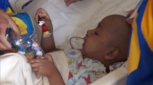 """Phoenix Murillo plays with a Mickey Mouse toy he was given during a visit from Eric Dickerson and """"Rampage"""" on Feb. 22, 2016. (Credit: KTLA)"""
