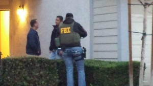 FBI officials are seen on Feb. 18, 2016, at a Corona home believed to be the residence of San Bernardino mass shooter Syed Rizwan Farook's brother. (Credit: Andrew Stephens)