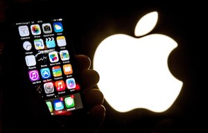 An illustration of an iPhone held up in front of the Apple Inc. logo taken Jan. 30, 2015. (Credit: PHILIPPE HUGUEN/AFP/Getty Images)