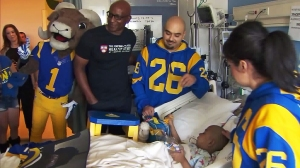 """Former Rams running back Eric Dickerson and mascot """"Rampage"""" visit Phoenix Murillo at Mattel Children's Hospital UCLA in Westwood on Feb. 22, 2016. (Credit: KTLA)"""