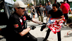 "A Ku Klux Klansman, left, struggles with a protester for an American flag after members of the KKK tried to start a ""White Lives Matter"" rally at Pearson Park in Anaheim on Saturday. Three people were treated at the scene for stab wounds, and 13 people were arrested. (Credit: Luis Sinco / Los Angeles Times)"
