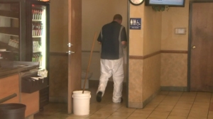 A worker cleans up after a newborn was found in the toilet of a West Covina Subway bathroom, shown, on Feb. 15, 2016. (Credit: KTLA)