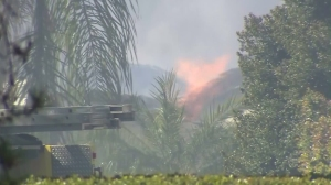 Flames are seen at a Chino home where a man was believed to be barricaded on March 9, 2016. (Credit: KTLA)