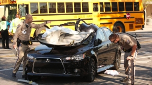 Two people were sent to the hospital in critical condition Thursday morning after their car collided with a Los Angeles Unified school bus in Watts. (Credit: Al Seib/Los Angeles Times)