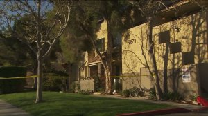 An apartment building was cordoned off by crime scene tape on March 12, 2016, after an alleged intruder was fatally shot in Canyon Country. (Credit: KTLA)