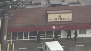 Law enforcement officials approach a Pasadena HoneyBaked Ham store where a pursuit driver was suspected of hiding out on March 3, 2016. (Credit: KTLA)