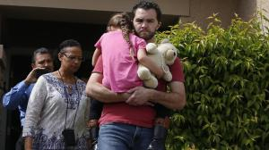 Rusty Page carries his foster daughter from his Santa Clarita home to waiting authorities on March 22, 2016. (Credit: Francine Orr / Los Angeles Times)