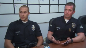 LAPD Officers Officer Garrett Brooks, left, and John Carlyle, right, talk to KTLA on March 29, 2016, about rescuing two people trapped in a car in South L.A. (Credit: KTLA)
