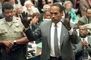O.J. Simpson shows the jury a new pair of Aris extra-large gloves, similar to the gloves found at the Bundy and Rockingham crime scene June 21, 1995, during his double-murder trial in Los Angeles. (Credit: VINCE BUCCI/AFP/Getty Images)