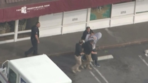 A suspected pursuit driver is detained outside a HoneyBaked Ham store in Pasadena on March 3, 2016. (Credit: KTLA)