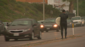 A surfer crosses the street leaving a beach in Malibu as rain begins to fall on March 11, 2016. (Credit: KTLA)