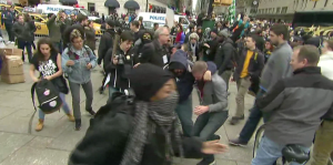 People come to the aid of a protester who was pepper sprayed during a march to Trump Tower in Manhattan on March 19, 2016. (Credit: CNN)