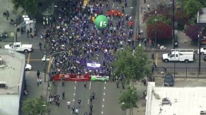 Protesters move through downtown Los Angeles in a march to demand a $15 minimum wage on April 14, 2016. (Credit: KTLA)