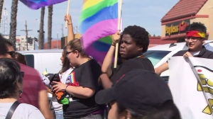 Student Kween Robinson holds a rainbow flag at a rally in support of LGBTQ community at Santee Education Complex on April 20, 2016. (Credit: KTLA)