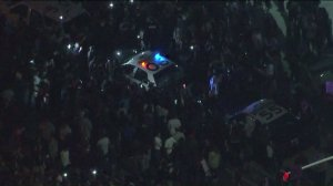 Several protesters swarm a Costa Mesa police car and try to overturn it following a Trump rally on April 28, 2016. (Credit: KTLA)
