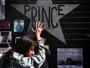 Prince fan Ann Sawatzky touches the star of music legend Prince who died suddenly at the age of 57, at the First Avenue club where he started his music career in Minneapolis, Minnesota, on April 23, 2016. (Credit: Mark Ralston/Getty Images)