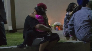 Mourners comfort each other outside Ulysses S. Grant Elementary School on April 12, 2016, when a sixth-grader died. (Credit: KTLA)