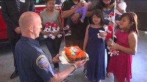 At a surprise birthday celebration in Huntington Beach on April 14, 2016, 8-year-old Adalyn Aguilar was reunited with Justin Schrey, the firefighter who helped deliver her. (Credit: KTLA)
