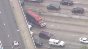 A TMZ tour bus briefly blocked in the driver of a Ford Mustang in a pursuit on the 101 Freeway on April 7, 2016. (Credit: KTLA)